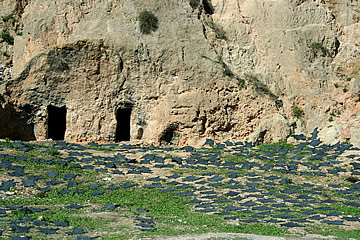 Black hides drying in the sun in front of cave dwellings